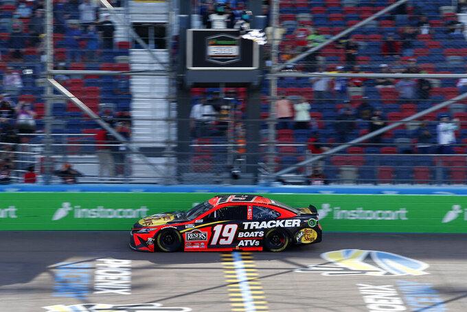 Martin Truex Jr. takes the checkered flag to win a NASCAR Cup Series auto race at Phoenix Raceway, Sunday, March 14, 2021, in Avondale, Ariz. (AP Photo/Ralph Freso)