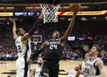 Sacramento Kings guard Buddy Hield, center, goes to the basket against San Antonio Spurs center LaMarcus Aldridge, left, as Spurs' DeMar DeRozan, second from right, and Jakob Poeltl, right, look on during the first quarter of an NBA basketball game Monday, Feb. 4, 2019, in Sacramento, Calif.(AP Photo/Rich Pedroncelli)