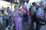 In this photo taken on Saturday, June 27, 2020, a woman holds a Russian national flag as she queues to board a bus to Russia at a bus stop in Donetsk, eastern Ukraine. Residents of separatist-controlled regions in eastern Ukraine who have Russian citizenship are traveling to Russia to vote on constitutional amendments that would allow President Vladimir Putin to remain in power until 2036. Authorities of the self-proclaimed Luhansk and Donetsk People's Republics have organized bus services to polling stations in the neighboring Rostov region in Russia, in what is seen by many as part of the wide-spread effort to boost turnout at the controversial plebiscite. (AP Photo/Alexei Alexandrov)