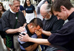 Hermelindo Che Coc, of Guatemala, kneels as Father Tom Carey, left, Rev. David Farley and Rev. Matthias Peterson-Brandt, right, pray over him before a required check-in with immigration enforcement authorities on Tuesday, July 10, 2018 in Los Angeles. Che Coc says his 6-year-old son feared he was dead after U.S. authorities separated the pair on the U.S.-Mexico border after they crossed into Texas in May. He says authorities told him he would be detained and his son was sent to a shelter in New York. (AP Photo/Richard Vogel)