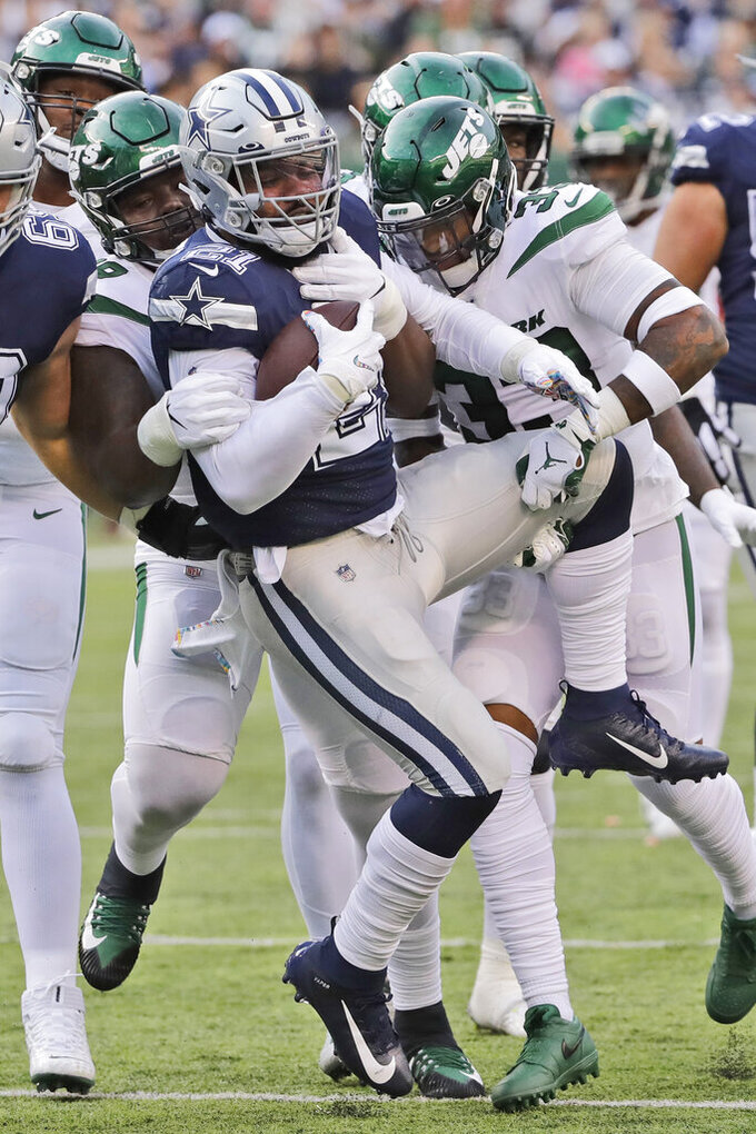 The New York Jets defenders tackle Dallas Cowboys' Ezekiel Elliott during the first half of an NFL football game, Sunday, Oct. 13, 2019, in East Rutherford, N.J. (AP Photo/Frank Franklin II)