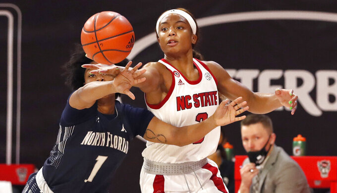 NC State's Kai Crutchfield (3) reaches for the ball against North Florida's Nubia Imani Benedith (1)  during the first half of an NCAA college basketball game at Reynolds Coliseum in Raleigh, N.C., Wednesday, Nov. 25, 2020. (Ethan Hyman/The News & Observer via AP)