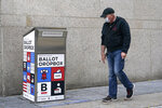 A pedestrian walks by the ballot drop box outside the Boston Public Library, Monday, Oct. 26, 2020, in Boston. Massachusetts election officials say a fire was set in the ballot drop box Sunday, holding more than 120 ballots in what appears to have been a