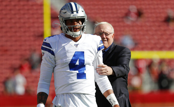 Dallas Cowboys owner Jerry Jones, right, stands behind quarterback Dak Prescott (4) as player warm up before an NFL preseason football game against the San Francisco 49ers in Santa Clara, Calif., Saturday, Aug. 10, 2019. (AP Photo/Josie Lepe)