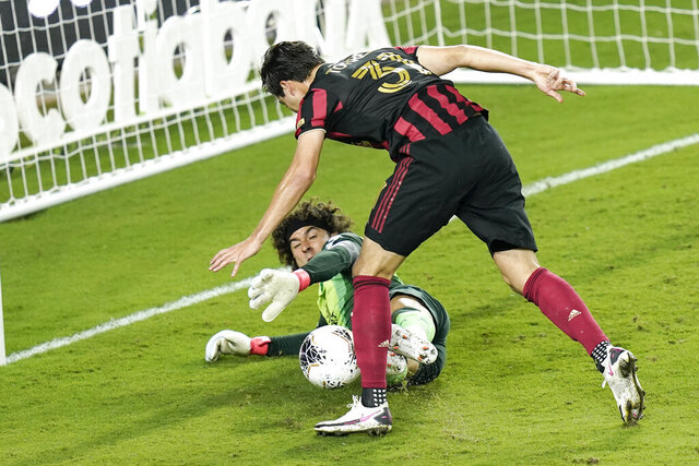 Club America goalkeeper Guillermo Ochoa, lower left, blocks a shot on goal by Atlanta United forward Erick Torres (31) during the second half of a CONCACAF Champions League soccer match, Wednesday, Dec. 16, 2020, in Orlando, Fla. (AP Photo/John Raoux)