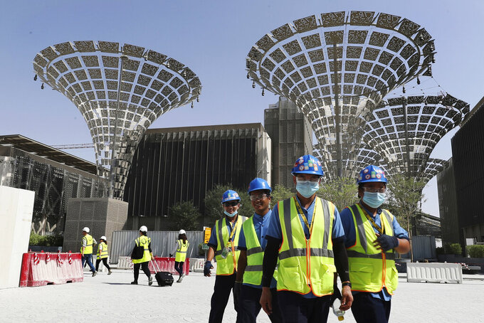 FILE - In this Oct. 8, 2019, file photo, technicians walk at the under construction site of the Expo 2020 in Dubai, United Arab Emirates. Dubai's Expo 2020 world's fair will be postponed to Oct. 1, 2021, over the new coronavirus pandemic, a Paris-based body behind the events said Monday, May 4, 2020. (AP Photo/Kamran Jebreili, File)