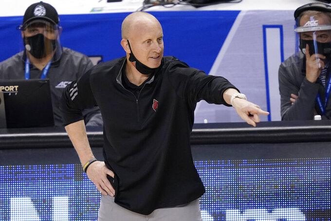 Louisville head coach Chris Mack directs his team during the first half of an NCAA college basketball game in the second round of the Atlantic Coast Conference tournament in Greensboro, N.C., Wednesday, March 10, 2021. (AP Photo/Gerry Broome)