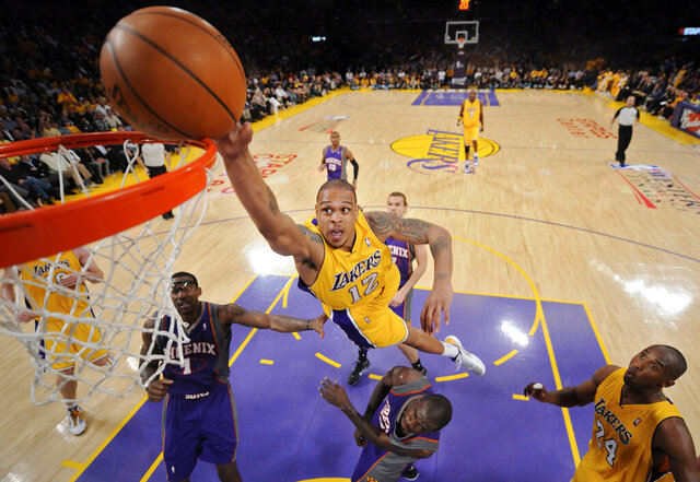 FILE - In this May 17, 2010, file photo, Los Angeles Lakers guard Shannon Brown, center top, attempts a dunk as Phoenix Suns forward Amare Stoudemire, left, and guard Jason Richardson, center bottom, defend while Lakers guard Kobe Bryant, right, watches during the second half of Game 1 of the NBA basketball Western Conference finals in Los Angeles. Former NBA player Brown faces charges in suburban Atlanta after he was accused of firing a rifle at two people who were looking at homes for sale, police said. Brown, 34, was arrested on a charge of aggravated assault stemming from an incident May 2, 2020, at his home in Tyrone, Georgia. He is free after he posted bond on Monday, May 4. (AP Photo/Mark J. Terrill, File)