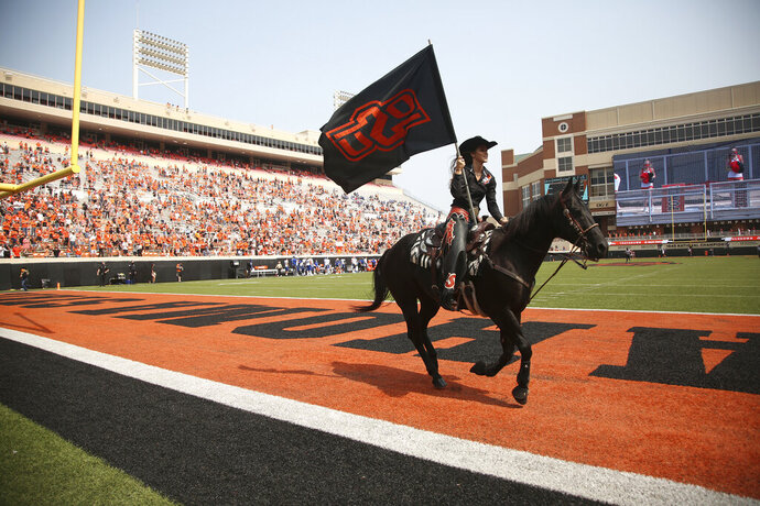 Oklahoma State student Harley Huff, of Evansville, Ind., guides Bullet across the field after an Oklahoma State touchdown during the second half of an NCAA college football game against Tulsa on Saturday, Sept. 19, 2020, in Stillwater, Okla. (John Clanton/Tulsa World via AP)