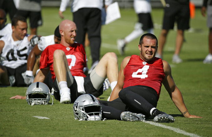Oakland Raiders quarterbacks Derek Carr, right, and Mike Glennon stretch during NFL football training camp Saturday, July 27, 2019, in Napa, Calif. (AP Photo/Eric Risberg)