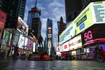 FILE - A screen displaying messages about COVID-19 light up a sparsely populated Times Square in New York on March 20, 2020. A new survey by The Actors Fund illustrates the depths of need created by the COVID-19 pandemic in the arts community. It reveals financial hardship, food insecurity and lost housing. (AP Photo/John Minchillo, File)