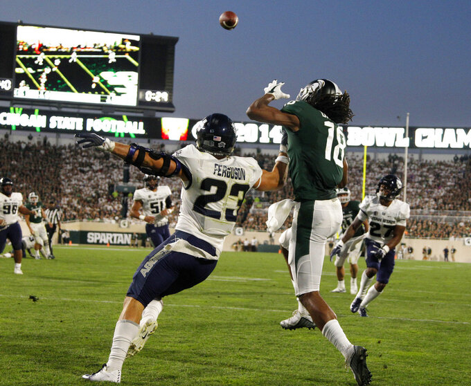 Michigan State's Felton Davis III (18) catches a pass in the end zone for a touchdown against Utah State's Gaje Ferguson (23) during the second quarter of an NCAA college football game, Friday, Aug. 31, 2018, in East Lansing, Mich. (AP Photo/Al Goldis)