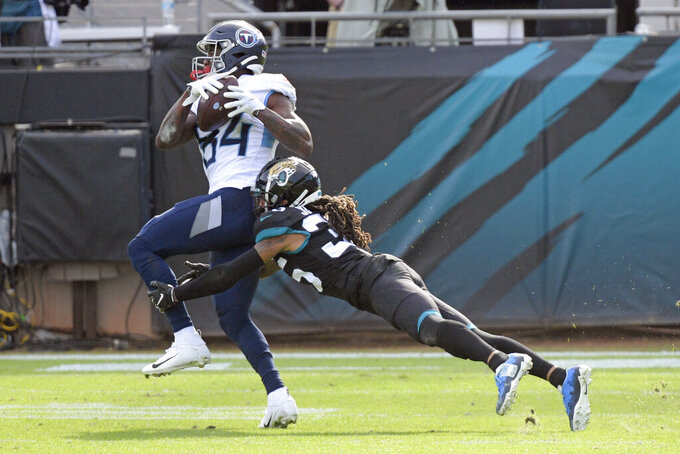 Tennessee Titans wide receiver Corey Davis, left, makes a reception before he is tackled by Jacksonville Jaguars cornerback Sidney Jones during the second half of an NFL football game, Sunday, Dec. 13, 2020, in Jacksonville, Fla. (AP Photo/Phelan M. Ebenhack)
