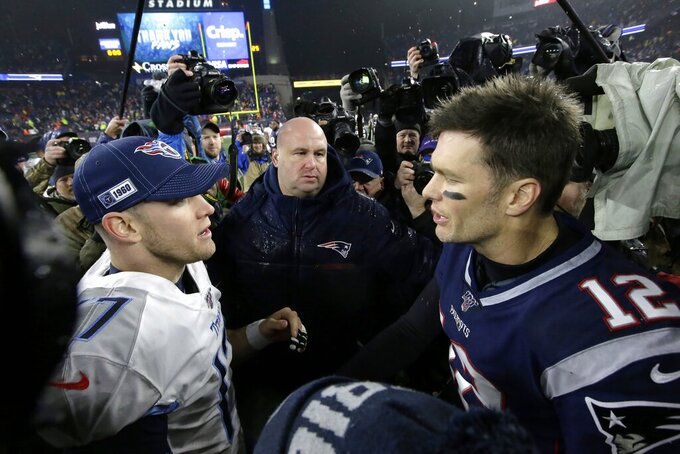 Tennessee Titans quarterback Ryan Tannehill, left, and New England Patriots quarterback Tom Brady speak at midfield after an NFL wild-card playoff football game, Saturday, Jan. 4, 2020, in Foxborough, Mass. (AP Photo/Steven Senne)