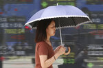 In this Wednesday, July 11, 2018, photo, a woman walks by an electronic stock board of a securities firm in Tokyo. Asian stock markets rose Thursday, July 12, 2018, following Wall Street's decline amid U.S.-Chinese trade tensions and oil prices recovered some of the previous day's steep losses. (AP Photo/Koji Sasahara)