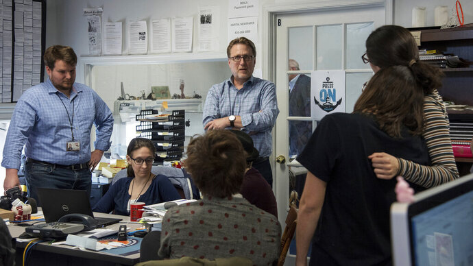 Editor Rick Hutzell, center, gives a speech to his staff including Chase Cook, Nicki Catterlin, Rachael Pacella, Selene San Felice and Danielle Ohl at the Capital Gazette in Annapolis, Md., Monday, April 15, 2019. Hutzell said Monday that his staff experienced some