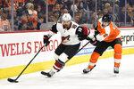 Arizona Coyotes' Brad Richardson, left, skates with the puck past Philadelphia Flyers' Travis Sanheim during the first period of an NHL hockey game, Thursday, Dec. 5, 2019, in Philadelphia. (AP Photo/Derik Hamilton)