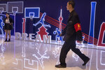 In this Friday, Oct. 11, 2019, photo, a security guard walks past neon light decor depicting basketball players and silhouette of iconic Chinese buildings in Beijing. When Houston Rockets' general manager Daryl Morey tweeted last week in support of anti-government protests in Hong Kong, everything changed for NBA fans in China. A new chant flooded Chinese sports forums: