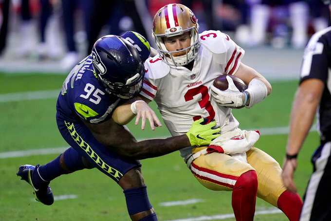 San Francisco 49ers quarterback C.J. Beathard (3) is sacked by Seattle Seahawks defensive end Benson Mayowa (95) during the first half of an NFL football game, Sunday, Jan. 3, 2021, in Glendale, Ariz. (AP Photo/Ross D. Franklin)