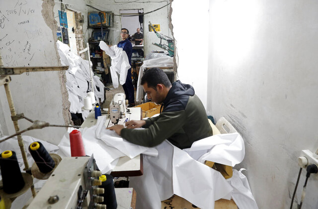 FLE - In this Monday, March 30, 2020 file photo, Palestinians make protective overalls meant to shield people from the coronavirus, to be exported to Israel, at a local factory, in Gaza City. For the first time in years, some sewing factories in the Gaza Strip are back to working at full capacity — producing masks, gloves and protective gowns, some of which are bound for Israel.(AP Photo/Adel Hana, File)