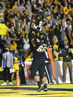 Appalachian State running back Camerun Peoples (6) celebrates with lineman Luke Smith (66) after scoring his first of three touchdowns of the first half against Marshall in an NCAA college football game, Thursday, Sept. 2, 2021 at Kidd Brewer Stadium in Boone, N.C. (Walt Unks/The Winston-Salem Journal via AP)