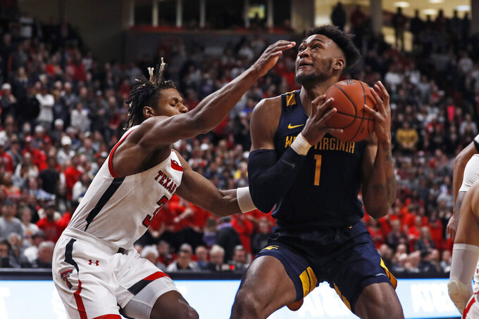 Texas Tech's Jahmi'us Ramsey (3) tries to block the shot by West Virginia's Derek Culver (1) during the first half of an NCAA college basketball game Wednesday, Jan. 29, 2020, in Lubbock, Texas. (AP Photo/Brad Tollefson)