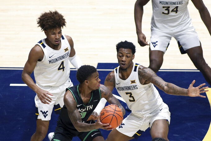 North Texas guard Javion Hamlet (3) is defended by West Virginia guard Miles McBride (4) and forward Gabe Osabuohien (3) during the second half of an NCAA college basketball game Friday, Dec. 11, 2020, in Morgantown, W.Va. (AP Photo/Kathleen Batten)