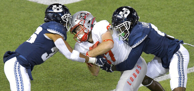 New Mexico wide receiver Andrew Erickson (87) is tacked by Utah State safety Jared Reed (36) and cornerback Cam Lampkin (6) during the first half of an NCAA college football game Thursday, Nov. 26, 2020, in Logan, Utah. (Eli Lucero/The Herald Journal via AP)