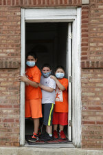 Mariano Ochoa, 9, left, poses for a photo with his brothers Victor Ochoa, 7, center, Jesus Ochoa, 5, at their home in Chicago, Friday, May 22, 2020. Chicago Run's at-home fitness programs have become an essential part of the Ochoa family's routine during the coronavirus pandemic. (AP Photo/Nam Y. Huh)