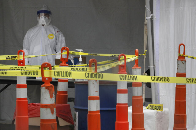 A medical worker stands in protective garments behind caution tape at a drive-through testing site for the coronavirus in a parking lot at Gillette Stadium, Sunday, April 5, 2020, in Foxborough, Mass. The site, which opened Sunday, is designated specifically for police officers, firefighters and other first responders who may have been exposed or are showing virus symptoms. The new coronavirus causes mild or moderate symptoms for most people, but for some, especially older adults and people with existing health problems, it can cause more severe illness or death. (AP Photo/Steven Senne)