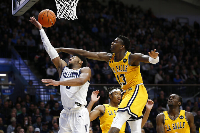Villanova's Justin Moore, left, tries to get a shot past La Salle's Saul Phiri during the second half of an NCAA college basketball game, Sunday, Dec. 1, 2019, in Villanova, Pa. (AP Photo/Matt Slocum)