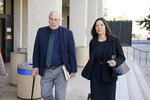 Geoffrey Carr, left, and May Mar, attorney's for Tiffany Li, walk out of the courthouse after opening statements were delayed in Li's trial, Thursday, Sept. 12, 2019, in Redwood City, Calif.  Li, a Chinese real estate scion, posted a $35 million bail after being charged with orchestrating the 2016 murder of her children's father. (AP Photo/Tony Avelar)
