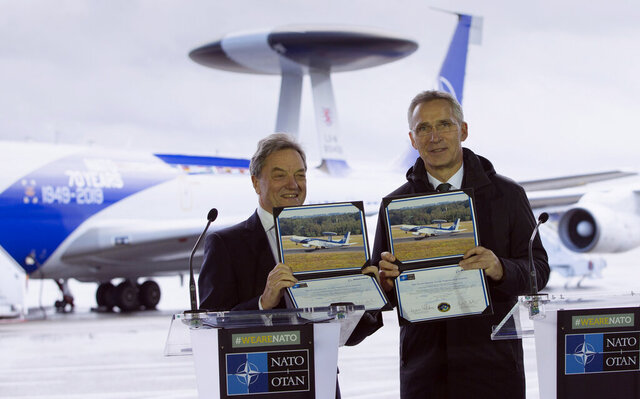 NATO Secretary General, Jens Stoltenberg, right, and the President of Boeing International, Sir Michael Arthur, hold up photos of an AWACS plane during a media conference at Melsbroek military airport in Melsbroek, Belgium, Wednesday, Nov. 27, 2019. NATO and the Boeing Company on Wednesday marked the signing of a 1 billion US dollar contract to modernize the Alliance's fleet of AWACS aircraft. This will ensure that NATO AWACS continue to support the Alliance's missions to 2035. (AP Photo/Virginia Mayo)