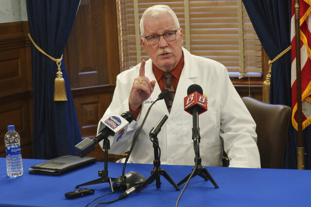 Dr. Lee Norman, the head of the Kansas Department of Health and Environment, answers questions from reporters during a news conference about the coronavirus pandemic, Wednesday, Oct. 7, 2020, at the Statehouse in Topeka, Kan. Norman says the state's hospitals will be stressed this fall and winter because of the pandemic and the state's annual flu season. (AP Photo/John Hanna)