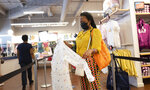 FILE - In this Tuesday, June 30, 2020, file photo, a woman shops for clothing in a Gap store during the coronavirus pandemic, in New York. U.S. employers likely rehired several million more workers in June, thereby reducing a Depression-level unemployment rate, but the most up-to-date data suggests that a resurgent coronavirus will limit further gains. (AP Photo/Mark Lennihan, File)