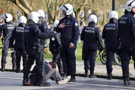 Police detain a man during protests at a park in Brussels, Thursday, April 1, 2021. Belgian police have clashed with a large crowd in one of Brussels largest parks, as thousands of revelers had gathered for an unauthorized event despite coronavirus restrictions. (AP Photo/Olivier Matthys)