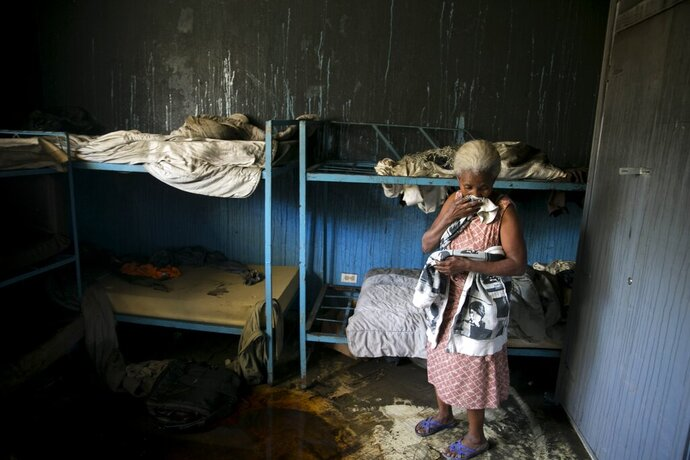 A staff worker of the Orphanage of the Church of Bible Understanding stands inside one of the bedrooms, the morning after a fire broke out at the facility in Kenscoff, on the outskirts of Port-au-Prince, Haiti, Friday, Feb. 14, 2020. A fire swept through this orphanage run by a Pennsylvania-based nonprofit group, killing over a dozen children, according to health care workers. (AP Photo/Dieu Nalio Chery)