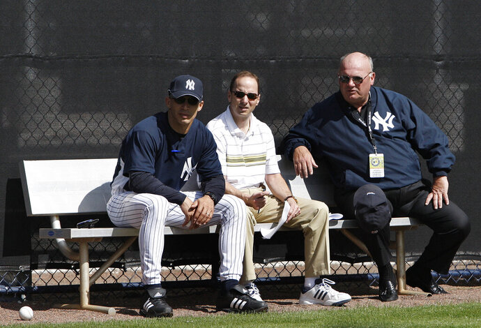 New York Yankees manager Joe Girardi, left, sits with general manager Brian Cashman, center, and senior vice president of baseball operations Mark Newman while watching spring training baseball workouts Friday, Feb. 15, 2008 in Tampa, Fla. Newman, a key front office executive for the New York Yankees during their run of five World Series titles from 1996 through 2009, was found dead Saturday, Sept. 12, 2020 at his home in Tampa, Fla. He was 71. (AP Photo/Julie Jacobson)