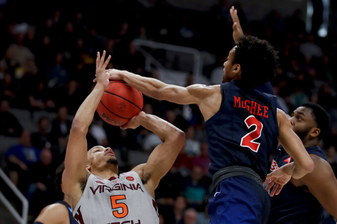 Liberty guard Darius McGhee (2) blocks a shot by Virginia Tech guard Justin Robinson (5) during the first half of a second-round game in the NCAA men's college basketball tournament Sunday, March 24, 2019, in San Jose, Calif. (AP Photo/Ben Margot)