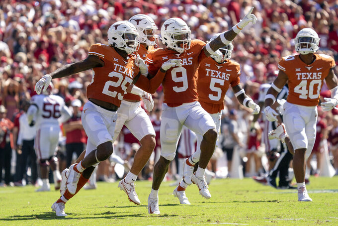 Texas defensive backs Josh Thompson (9) and B.J. Foster (25) celebrate Foster's interception against Oklahoma during the first half of an NCAA college football game at the Cotton Bowl, Saturday, Oct. 9, 2021, in Dallas. (AP Photo/Jeffrey McWhorter)