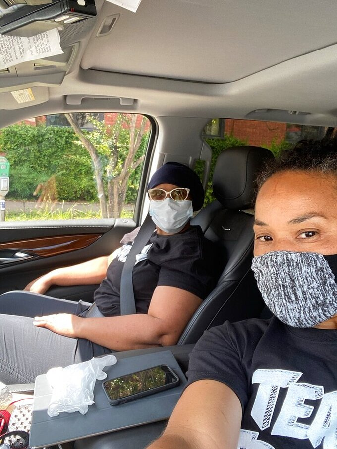 In this undated photo provided by Dawn Staley, South Carolina women's basketball coach Dawn Staley, right, and her sister, Tracey Underwood, head home after Underwood's first treatment at the Prisma Health Richland Hospital in South Carolina.  Dawn Staley's passion is evident when she's on a basketball court. But when her sister was diagnosed with leukemia last year it wasn't about a game, it was life and death. (Dawn Staley via AP)