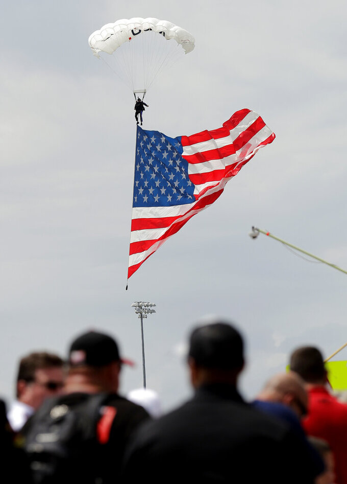 A man parachutes into Chicagoland Speedway with a large U.S. flag during the national anthem before the NASCAR Xfinity Series auto race at Chicagoland Speedway in Joliet, Ill., Saturday, June 29, 2018. (AP Photo/Nam Y. Huh)
