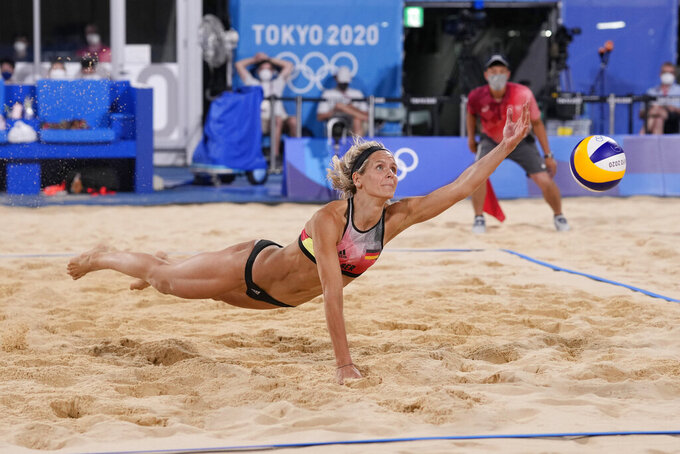 Laura Ludwig, of Germany, dives for the ball during a women's beach volleyball match against Japan at the 2020 Summer Olympics, Monday, July 26, 2021, in Tokyo, Japan. (AP Photo/Petros Giannakouris)