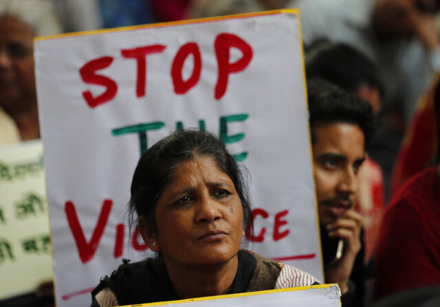 Activists from different organizations hold banners calling for peace and communal harmony following violence in New Delhi, India, Wednesday, Feb. 26, 2020. At least 20 people were killed and 189 injured in three days of clashes in New Delhi that coincided with U.S. President Donald Trump's first state visit to India, with the death toll expected to rise as hospitals continue to take in the wounded, authorities said Wednesday. (AP Photo/Rajesh Kumar Singh)