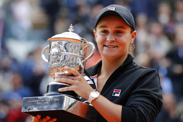 FILE - In this June 8, 2019, file photo, Australia's Ash Barty holds the trophy as she celebrates winning her women's final match of the French Open tennis tournament against Marketa Vondrousova of the Czech Republic in two sets 6-1, 6-3, at the Roland Garros stadium in Paris. Barty has joined the ranks of high-profile players expressing concern over the staging of the U.S. Open while there's still so much uncertainty in the coronavirus pandemic. The women's No. 1 hasn't had the chance yet to defend her French Open title because all elite tennis competition is shuttered. (AP Photo/Christophe Ena, File)
