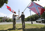 FILE - In this Thursday, June 25, 2015 file photo, activists hold Confederate flags near the monument for Confederate President Jefferson Davis on Monument Avenue in Richmond, Va. The monument was vandalized the previous night, spray-painted with the phrase