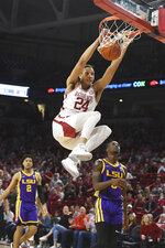 Arkansas forward Ethan Henderson (24) dunks the ball over LSU defenders Trendon Watford (2) and Emmitt Williams (5) and during the first half of an NCAA college basketball game Wednesday, March 4, 2020, in Fayetteville, Ark. (AP Photo/Michael Woods)