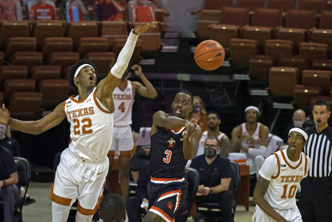 Sam Houston State guard Demarkus Lampley (3) passes the ball against Texas forward Kai Jones (22) during the first half of an NCAA college basketball game, Wednesday, Dec. 16, 2020, in Austin, Texas. (AP Photo/Michael Thomas)
