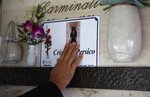 Rev. Mario Carminati touches a pictures of his nephew Christian Persico, at a cemetery in Casnigo, near Bergamo, Italy, Sunday, Sept. 27, 2020. As the world counts more than 1 million COVID victims, the quiet of everyday life and hum of industry has returned to Bergamo, which along with the surrounding Lombardy region was the onetime epicenter of the outbreak in Europe. But the memory of those dark winter days, and the monumental toll of dead they left behind, has remained with those who survived only to see the rest of the world fall victim, too. (AP Photo/Antonio Calanni)