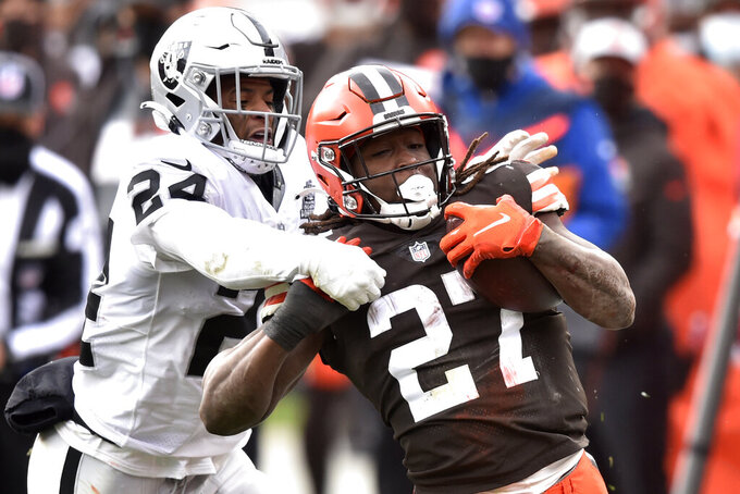 Cleveland Browns running back Kareem Hunt (27) runs for a first down as Las Vegas Raiders strong safety Johnathan Abram (24) tries to tackle him during the first half of an NFL football game, Sunday, Nov. 1, 2020, in Cleveland. (AP Photo/David Richard)